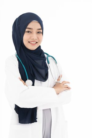 Portrait of Muslim confident female doctor medical professional sitting in examination room in hospital clinic. Positive face expression