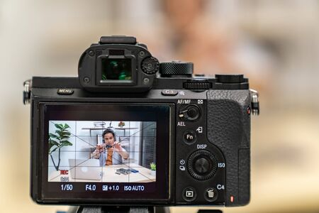 asian male IT vlogger and blogger live Technology upgrand on laptop memory ram using digital camera recording live vlog video. Online influcencer on social media concept. Focus on camera.