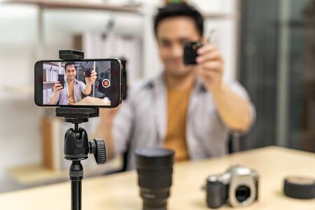 Young asian male IT vlogger and blogger live about digital camera Technology upgrand using mobile phone to recording live vlog video. Online influcencer on social media concept. Focus on camera.