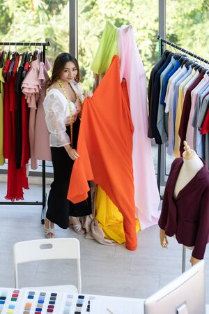 Top view of  young adult fashion designer using measuring tape to measure suit arm at her atelier studio as sole owner. Using for entrepreneur startup concept.