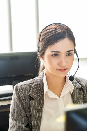 Portrait of Asian young adult friendly and confidence operator call centre with headsets in a call center as customer service and technical support.