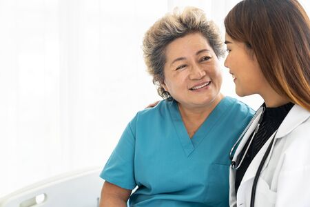 Young female doctor in uniform hugging and smiling to old elderly woman patient during a visit in hospital ward Stock Photo