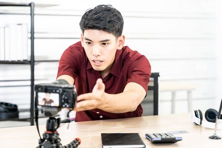 Young asian male blogger setting up camera for recording live vlog video tutorial session at home. IT blogging or vlogging, social media hobby broadcasting, or online learning course concept.