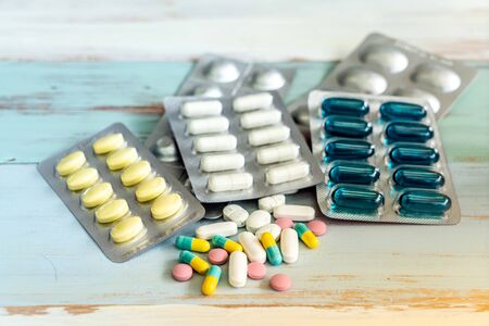 Variety of medicine spilling and pill bottle on vintage wooden background. Using as health care and medical cure and pharmaceutical industry background.