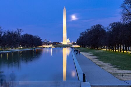 Washington Monument in new reflecting pool from Lincoln Memorial at sunset night.This monument is obelisk on the National Mall one of landmark of Washington DC USA.