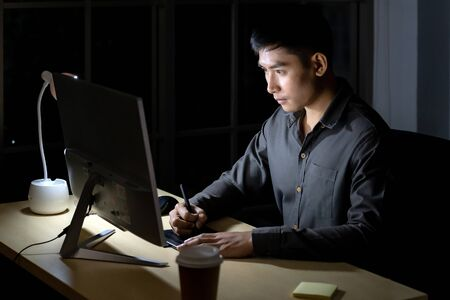 Young adult asian businessman and woman working late at night in their office with desktop computer and laptop. Using as hard working and working late concept. Banque d'images