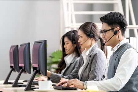 Young adult friendly and confidence operator asian man agent with headsets working in a call center with his colleague team working as customer service and technical support workplace in background. Stock Photo