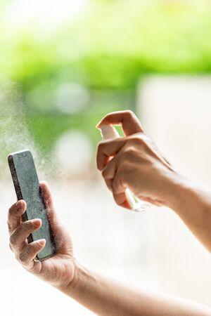 close-up cleaning mobile phone using alocohol spray from bottle spraying, disinfection for safety prevent and protect from infection of virus and germ Covid-19 coronavirus world pandemic.