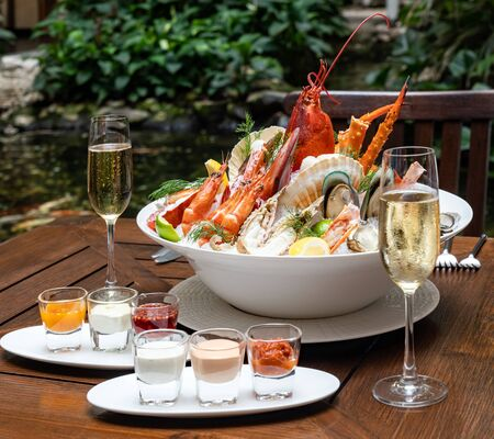 Bowl of gourmet fresh seafood on ice with savory sauce serve with white wine glass on vintage wooden table. Restaurant gastronomy food and drink consumerism concept. Stock Photo