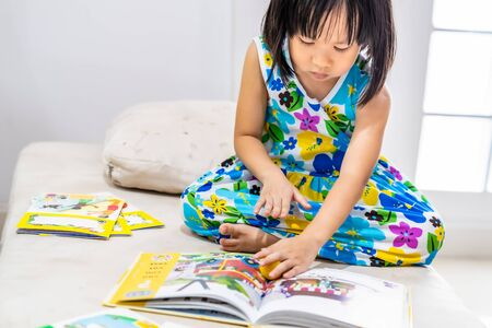 Asian girl child reading interactive book in living room at home as home schooling while city lockdown because of covid-19 pandemic across the world. Home Scholling prepare for Preschool concept.