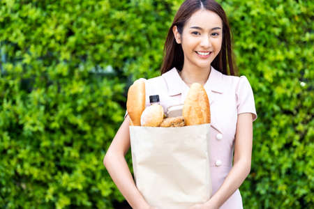 Portrait of attractive and smile asian woman holding grocery bag buy from supermarket. Food and drink and consumerism buying concept.