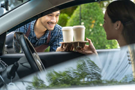 Waiter giving hot coffee cup with disposable tray and bakery bag through car window to customer at drive thru service station. Drive thru is popular service after coronavirus covid-19 pandemic.