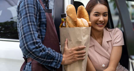 Delivery staff giving grocery bag set to asian customer woman at drive thru service station of Supermarket. Drive thru is popular service and new normal after coronavirus covid-19 pandemic.