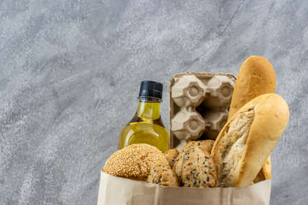 Grocery bag with egg cooking oil and variety of bread in disposalable paper bag on gray vintage loft background. Bakery food and drink and grocery concept for delivery.