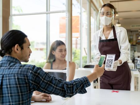 Asian customer scan QR code online menu from waitress with face mask and face shield. Customer sat on social distancing table for new normal lifstyle in restaurant after coronavirus covid-19 pamdemic.