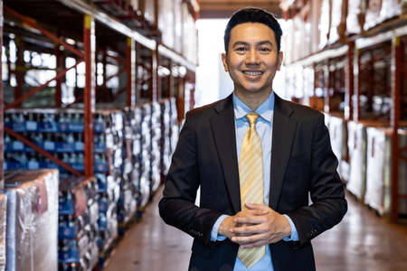 Portrait of asian confidence businessman investor stand in large factory and distribution warehouse environment. Business owner and investment concept.