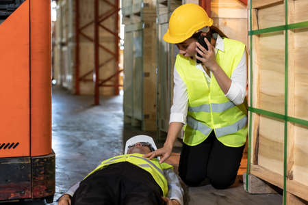 Asian worker Call an ambulance after warehouse manager lying down on warehouse floor after accident from forklift. Using for safety first and business insurance concept. Фото со стока