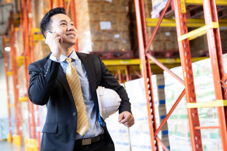 Portrait of asian confidence businessman investor stand and making a call with mobile phone  in large factory and distribution warehouse environment. Business investment merger acquisitions concept.