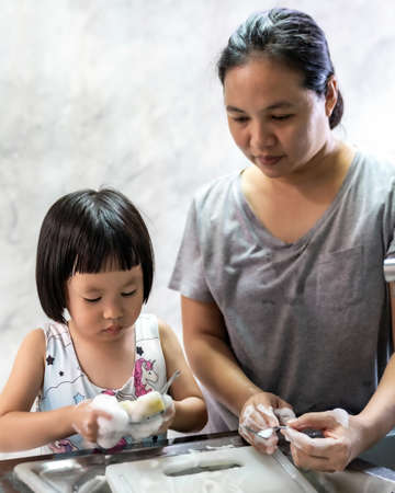 Asian girl washing dish and tableware with her mom, housework for child make executive function for kid. Houseworking for kid lifstyle and family concept.