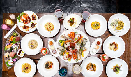 Table top view premium variety of international food in restaurant of lobster shrimp steak beef lamb pasta spaghetti risotto rice sushi sashimi and wine using for buffet food drink background. 版權商用圖片