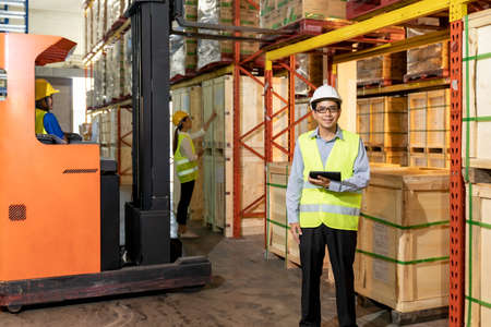 Portrait of Asian warehouse manager hold digital tablet with warehouse worker operate forklift to check inventory in background. Reopening business warehouse technology and logistic concept.