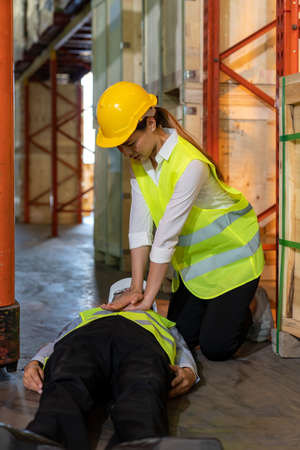 Asian worker do Cardiopulmonary Resuscitation CPR after warehouse manager lying down on warehouse floor after accident from forklift. Using for safety first and business insurance concept.