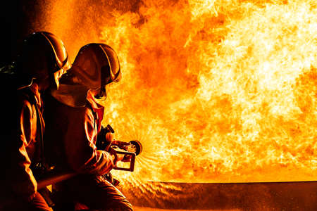 Firefighters using Twirl water fog type fire extinguisher to fighting with the fire flame from oil to control fire not to spreading out. Firefighter and industrial safety concept.