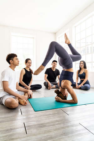 Asian yoga female coach or instructor wear sportswear bra pants show student in fitness studio class poseture of headstand pose. Yoga Practice Work out exercise and healthy lifestyle concept. Standard-Bild