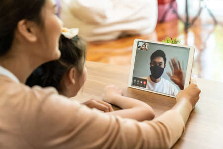 Quarantine father video conference call with his family of mom and daughter while stay in state quarantine. Technology and family reunion new normal while coronavirus covid-19 pandemic. Banco de Imagens