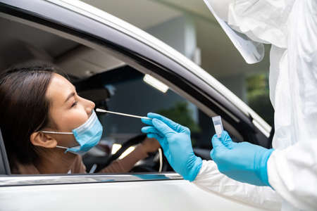 Portrait of asian woman drive thru coronavirus covid-19 test by medical staff with PPE suit by nose swab. New normal healthcare drive thru service and medical concept.