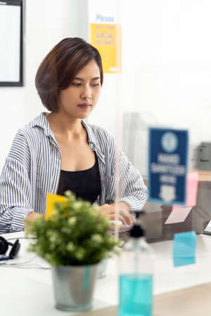 Businesswoman working in home office with social distance using screen partition to prevent from coronavirus COVID-19 spreading. New normal concept after pandemic. Banque d'images - 154872074
