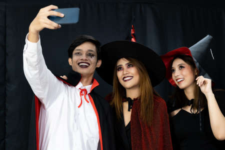 Group of friends asian young adult people celebrate a Halloween party carnival Festival. They wear Halloween costumes take selfie photographing. Halloween celebrate and international holiday concept. Banque d'images - 154872076