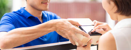 Panoramic Asian woman sign electronic signature to portable mobile device after receive packge from male delivery man in blue shirt. Package shopping delivery and digital sign concept. Banque d'images - 154872080
