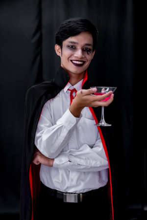 Portrait of asian young adult teenage man wear Halloween costume cloth hold glass of cocktail for Halloween party background. Halloween celebrate and international holiday concept. Banque d'images - 154872081