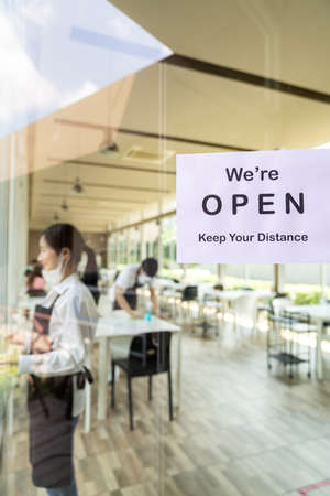 Reopening restaurant signage with social distance for new normal restaurant with background of asian waiter and waitress prepare restaurant before open. New normal restaurant lifestyle concept. Banque d'images - 154872094