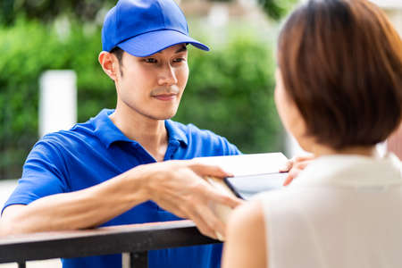 Asian deliver man handling package box to asian woman in front of house and female customer sign electronic signature to portable mobile device. Package shopping delivery and digital sign concept. 版權商用圖片