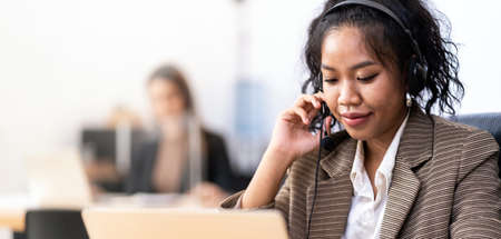 Panorama Young adult friendly confidence operator Mixed race of African asian woman with headsets working in a call center with her colleague in background. Call center and telemarketing sale concept.