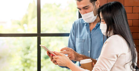 Panoramic Two business person standing for brainstorm and discuss their work with digital tablet. They wear protective face mask in new normal office preventing coronavirus COVID-19 spreading. Banque d'images - 155226632