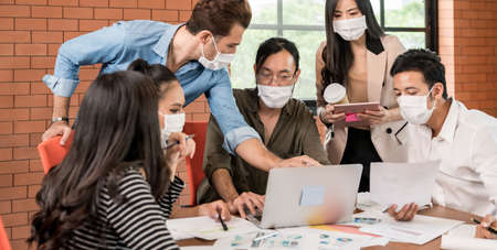 Panoramic group of asian caucasian business team meeting and brainstorm in meeting room after office reopen, they wear protective face mask as new normal practice to prevent coronavirus infection. Banque d'images - 155226635