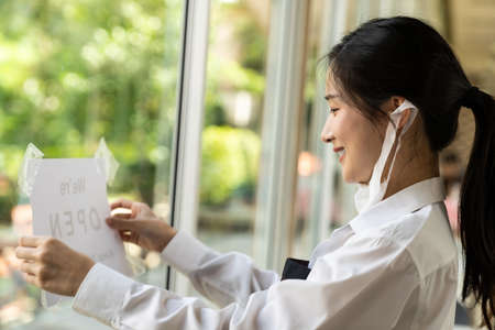 Asian female waitress putting on open signage with social distance for new normal restaurant. New normal restaurant lifestyle concept. Banque d'images - 155226636