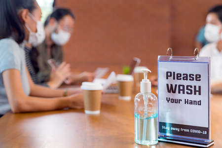 Signage of Hand sanitizer alcohol gel in meeting room with background of Asian team business people working and brainstorm. They wear face mask in new normal office to prevent covid-19 virus spreading