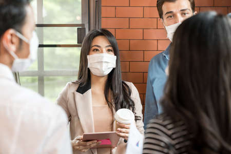 Group of business worker team meeting and brainstorm for startup new business. They wear protective face mask in new normal office preventing coronavirus COVID-19 spreading.