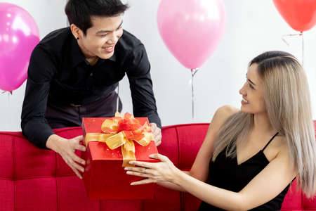 Portrait of couple holding gift box present celebraing New Year Party festival holiday in living room Banque d'images