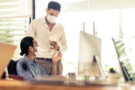 Two asian businessman talk discuss their work in morning after office reopen due to coronavirus COVID-19 pandemic. They wear protective face mask to prevent infection. New normal office life concept. Banque d'images - 155226645