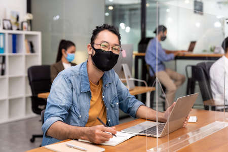 Portrait of asian office employee businessman wear protective face mask work in new normal office with interracial colleague in background as social distance practice prevent coronavirus COVID-19.
