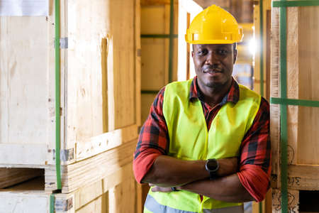 Portrait of african black warehouse worker standing and crossed his arms smile and looking at camera in large warehouse distribution center. Using in business warehouse and logistic concept.