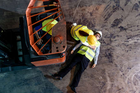 Asian worker do Cardiopulmonary Resuscitation CPR after warehouse manager lying down on warehouse floor after accident from forklift. Using for safety first and business insurance concept. Top view. Banque d'images