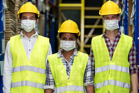 Portrait of Interracial group Asian African and Caucasian warehouse workers team wear face mask to prevent COVID-19 coronavirus infection in distribution center. Business teamwork concept. Banque d'images