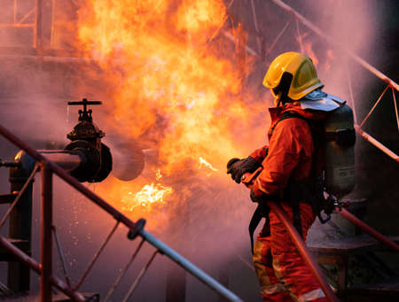Firefighter using water fog type fire extinguisher to fighting with the fire flame from oil pipeline leak and explosion on oil rig and natural gas station. Firefighter and industrial safety concept. Banque d'images