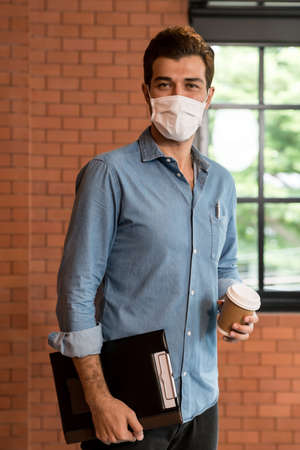 Portrait of middle east caucasian businessman with takeout coffee cup and clipboard in meeting room after lunch break. He wear face mask as new normal office preventing coronavirus COVID-19 spreading. Banque d'images